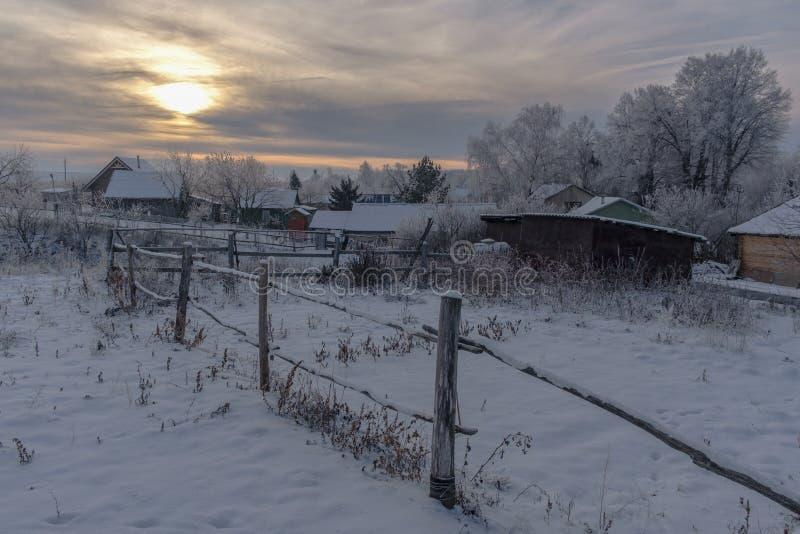 Tarde hermosa del paisaje del invierno en un pequeño pueblo fotos de archivo