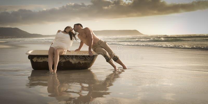Tarde hermosa joven del gasto de los pares en la playa con la tina de baño vieja imagenes de archivo
