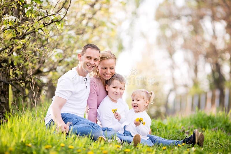 Tarde nova feliz da mola da despesa da família de quatro membros junto imagens de stock royalty free