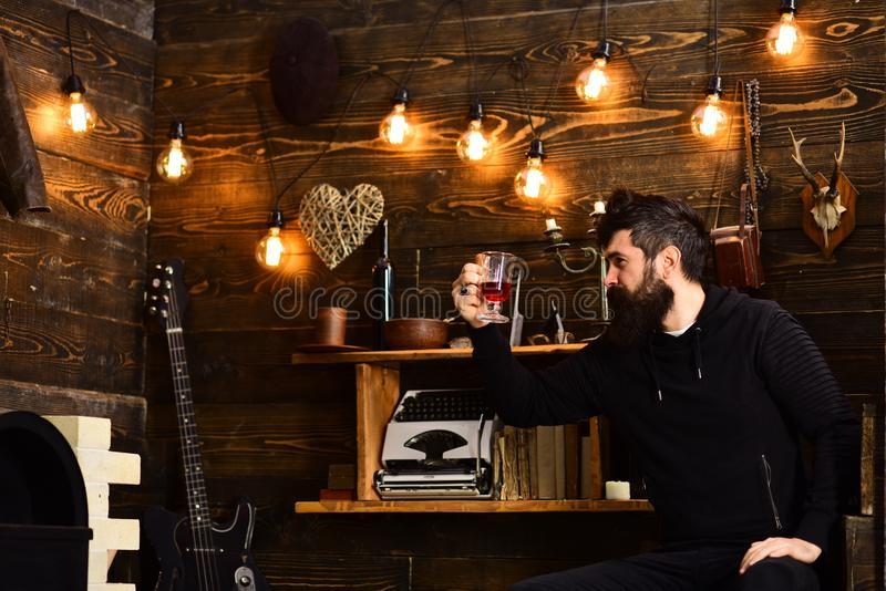 Tarde relajante El hombre con la barba sostiene el vidrio de la bebida estacional caliente reflexionada sobre del vino Individuo  imagen de archivo
