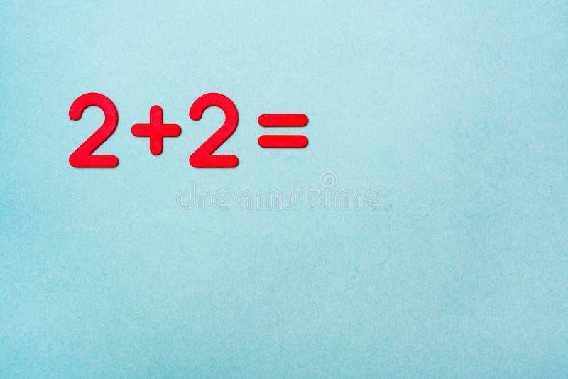 A tarefa da escola - dois mais dois - é alinhada com números vermelhos imagem de stock royalty free