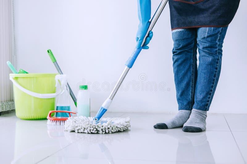 Tarefas domésticas e conceito da limpeza, jovem mulher feliz na RUB azul fotos de stock