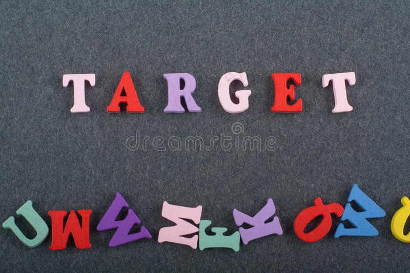 TAREGET λέξη στο μαύρο υπόβαθρο πινάκων που συντίθεται από τις ζωηρόχρωμες ξύλινες επιστολές φραγμών αλφάβητου abc, διάστημα αντι στοκ φωτογραφίες