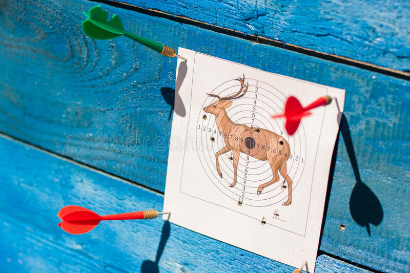 Target on a blue background. Firing at a target. Target on a blue background. The target punctured with a dart. Accurate shooting on a target. Firing at the royalty free stock photo