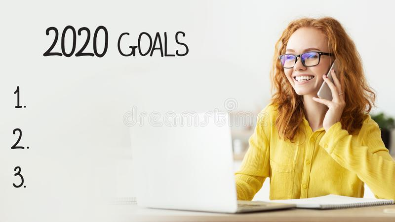 Target Business development to success in 2020, goals checklist. Target Business development to success in 2020. Cheerful girl talking on phone and working on stock image