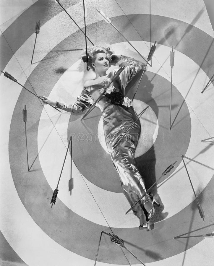 A target of desire, a young woman lying on the bulls eye with arrows around her royalty free stock photography