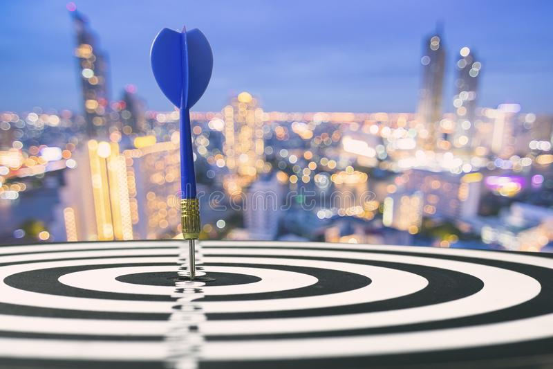 target and goal concept, blue dart on board with night city back royalty free stock photo