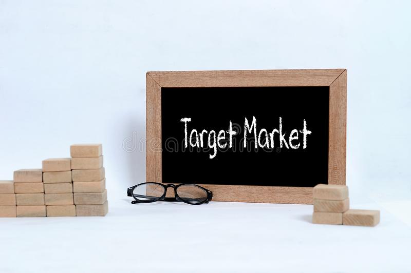 Target Market handwritten with white chalk on a blackboard. Eye glasses and Wood block stacking as step stair symbol of business c royalty free stock image