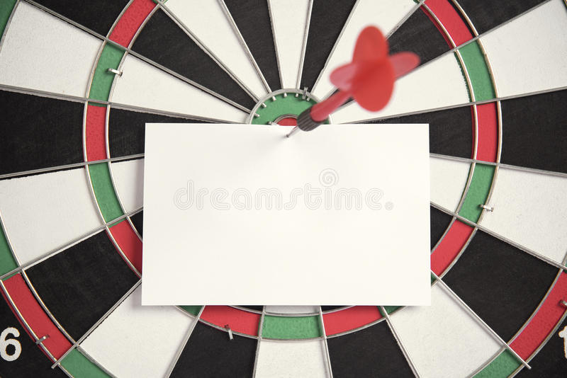 Target red arrow and paper note on center of dartboard. royalty free stock image