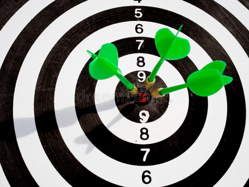 Target with three green dart focus on bull`s eye, Setting challenging business goals And ready to achieve the goal with teamwork. Concept royalty free stock photography