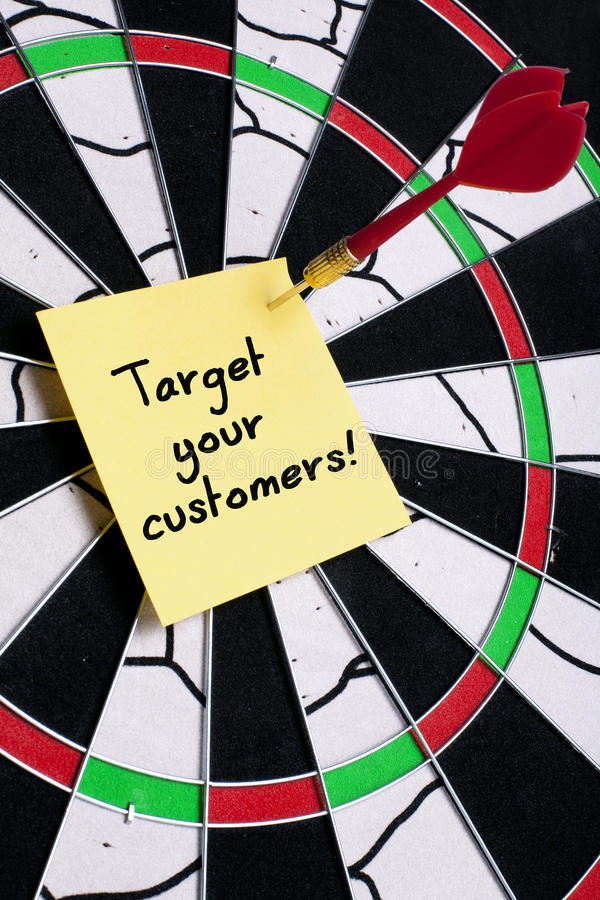 TARGET YOUR CUSTOMERS. Note hit on dartboard stock photography