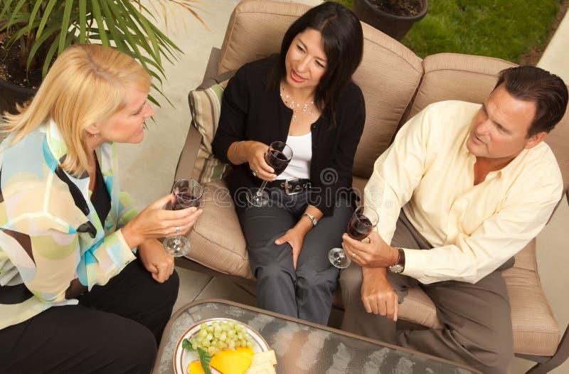 target0_0_ przyjaciół patia trzy wino zdjęcie stock