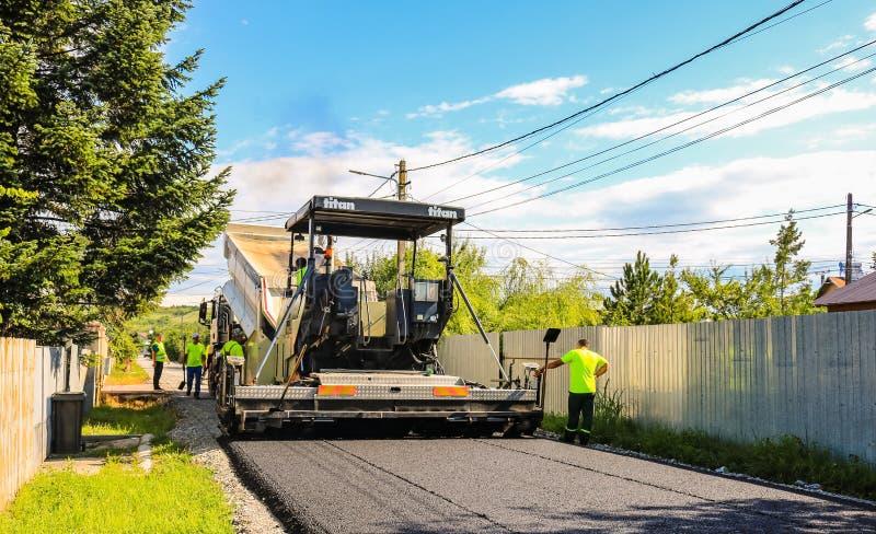 Targoviste,罗马尼亚- 2019年 等待重的翻斗车的工作者卸载在一台准备的沥青摊铺机的新和热的沥青混合 库存图片