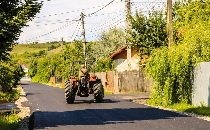 Targoviste, Ρουμανία - 2019 Farmer στους κόκκινους γύρους τρακτέρ στη νέα άσφαλτο στο φως του ήλιου στοκ φωτογραφίες με δικαίωμα ελεύθερης χρήσης