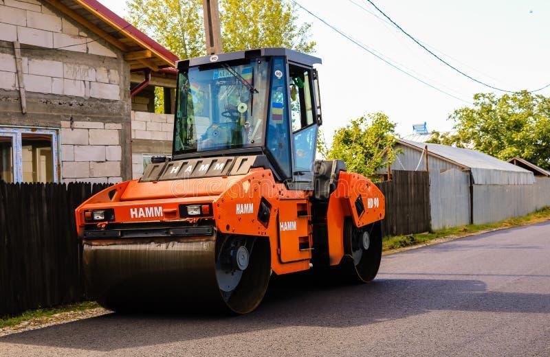 Targoviste, Румыния - 2019 Оранжевый ролик дороги отжимая горячий асфальт Конструкция новой дороги с поддержкой от европейского стоковые изображения rf