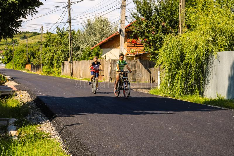 Targoviste, Rom?nia - 2019 Crianças felizes que montam bicicletas no asfalto novo fotos de stock
