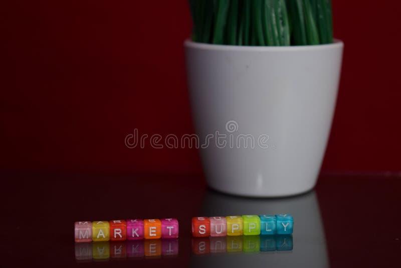 Targowej dostawy tekst przy kolorowym drewnianym blokiem na czerwonym tle Biurka biuro i edukacji pojęcie zdjęcia stock