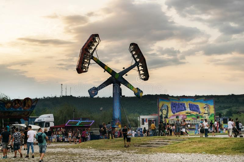 Targu Jiu. Romania. August, 25, 2019- in the amusement park at sunset. The sky covered with black clouds foretells the start of. Rain. Adults and children are stock photography
