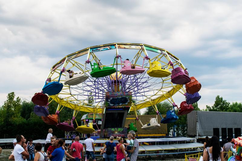 Targu Jiu. Romania. August, 25, 2019- in the amusement park at sunset. The sky covered with black clouds foretells the start of. Rain. Adults and children are royalty free stock photography