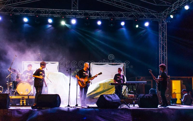 Targu Jiu, Romania. August, 25, 2019- a children`s band and an adult guitarist, perform on a rock music festival.  stock photography