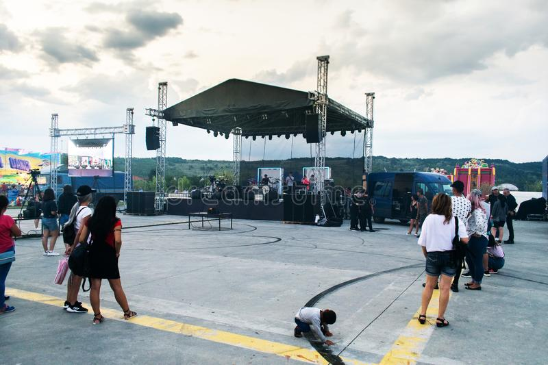 Targu Jiu, Romania. August, 25, 2019- The stage prepared before the start of a concert. People are starting to gather to attend. The concert. The sky covered stock photo