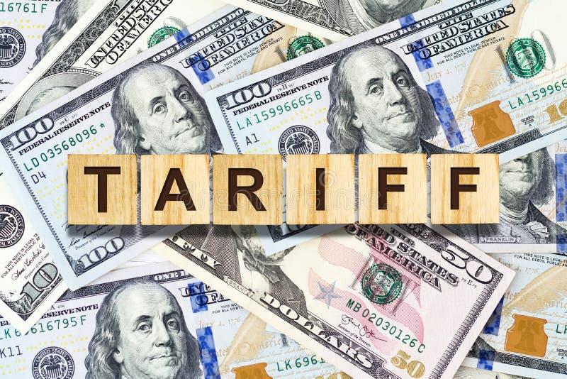 Tarif, Aufschrift auf den Holzklötzen auf dem Hintergrund der Dollarbanknoten Gesch?ft, Finanzierung lizenzfreie stockfotografie