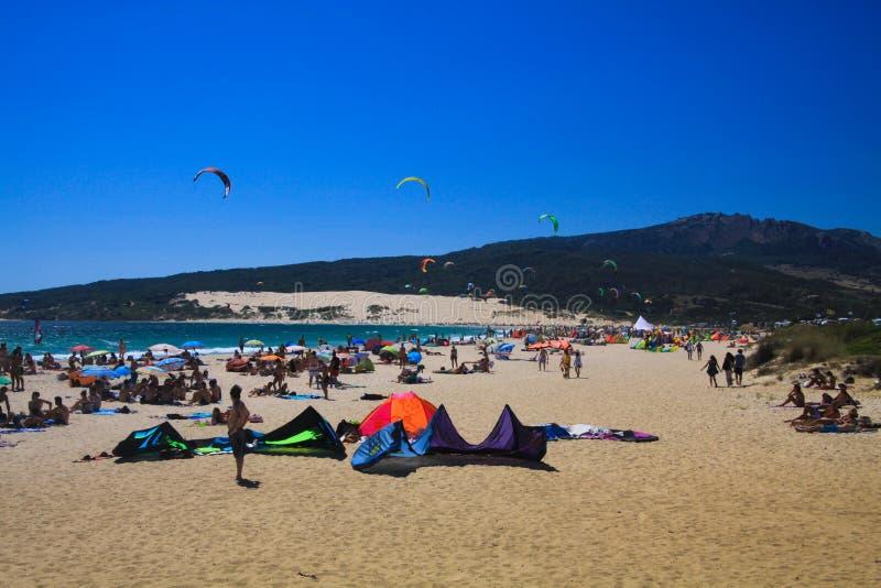 TARIFA COSTA DE LA LUZ, PLAYA DE BOLONIA, ESPAÑA - JUNIO, 18 2016: Personas que practica surf de la cometa en la playa en España imagen de archivo libre de regalías