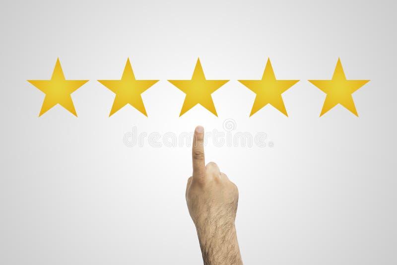 tarifa 5 estrellas La mano hace clic en cinco estrellas amarillas para aumentar el grado Comentarios del cliente, grado, concepto foto de archivo libre de regalías