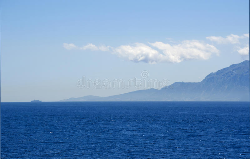 Tarifa, Spain, Andalusia, Iberian Peninsula, Europe. Strait of Gibraltar, 22/04/2016: a ship in the distance and the Moroccan coast in the waters that connect stock images