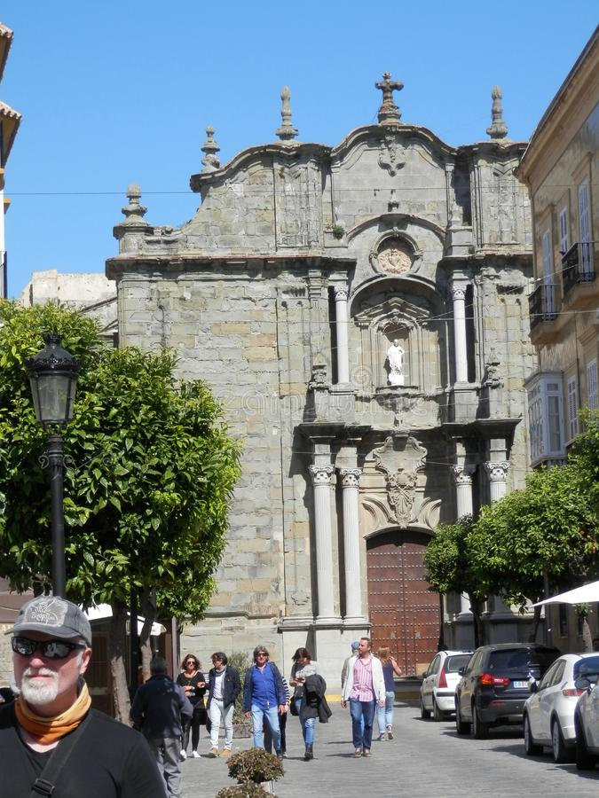 People walking in front ofSt Matthews church, Tarifa, Cadiz Province, Andalusia, Spain. Tarifa, Spain - March 31, 2019: Front view of St Matthews church with stock photos