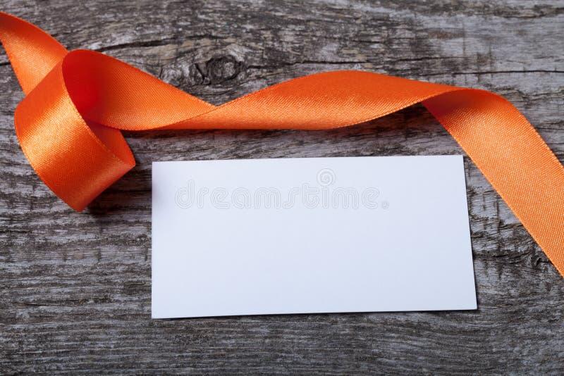 Tarjeta anaranjada de la cinta y de visita en el viejo tablero de madera gris para el CCB fotografía de archivo