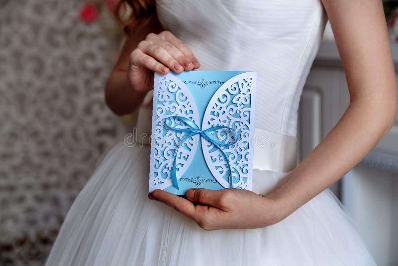 Tarjeta azul de la invitación de la boda en manos fotografía de archivo