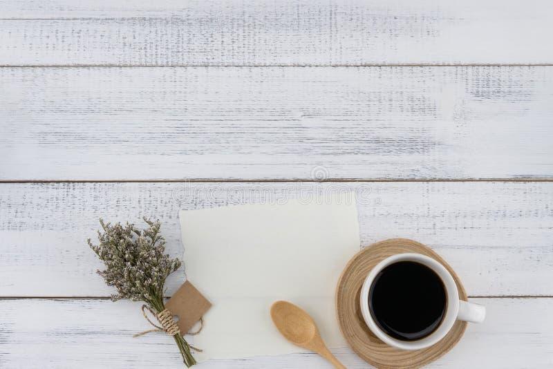 Tarjeta blanca en blanco y una taza de café con el ramo del caspia foto de archivo