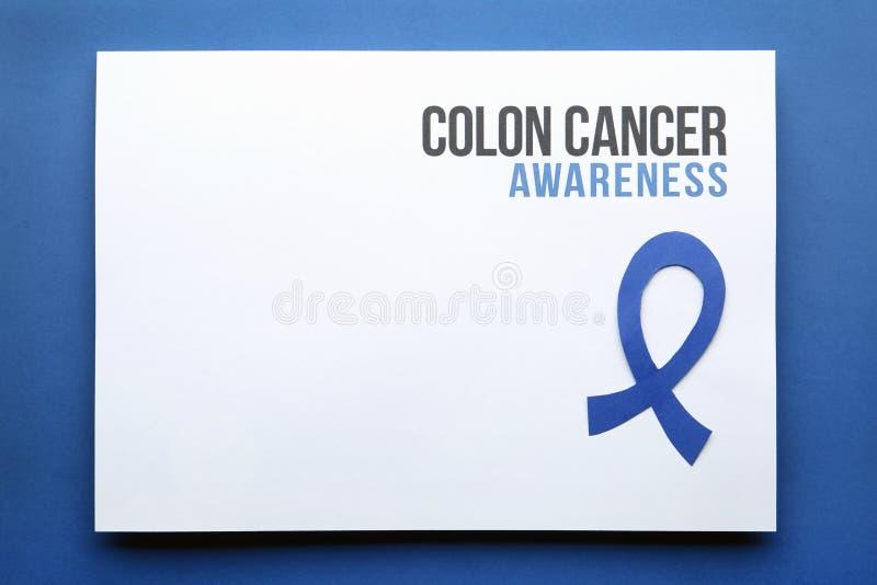 Tarjeta con CONCIENCIA de las palabras CÁNCER DE COLON y cinta azul en el fondo del color, visión superior foto de archivo libre de regalías