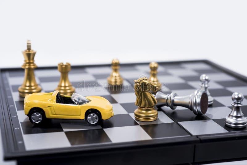 Tarjeta de ajedrez aislada en el fondo blanco Figuras de oro y de plata con el pequeño coche amarillo imagenes de archivo