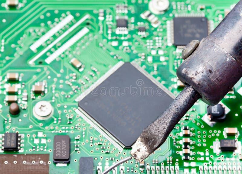 Tarjeta de circuitos de ordenador con soldar del hierro imagen de archivo