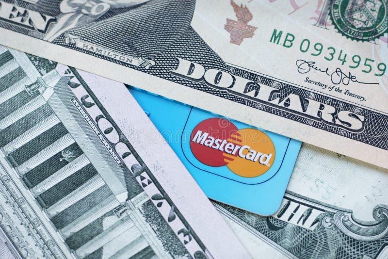 Tarjeta de crédito con el primer del logotipo de Mastercard y de los billetes de banco del dólar americano Mosc?, Rusia - mayo de foto de archivo