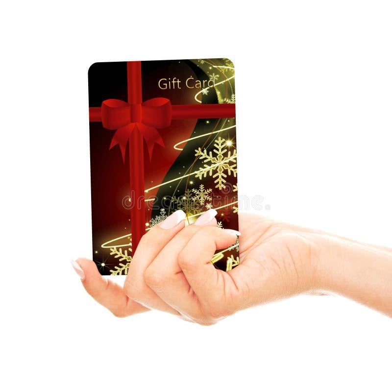 Tarjeta De Crédito De La Navidad Holded A Mano Sobre Blanco Fotografía de archivo