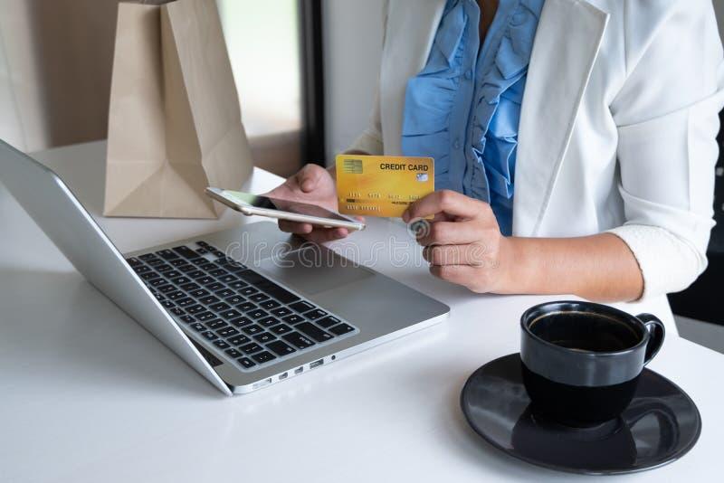 Tarjeta de crédito del uso de la mujer para las compras en línea en su ordenador portátil y teléfono imagen de archivo libre de regalías
