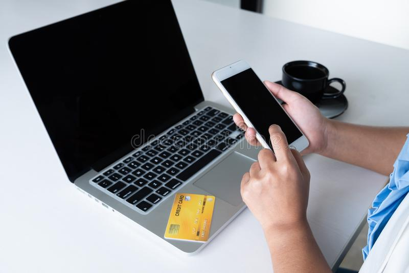 Tarjeta de crédito del uso de la mujer para las compras en línea en su ordenador portátil y teléfono imagen de archivo