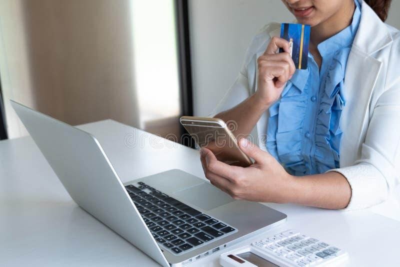 Tarjeta de crédito del uso de la mujer para las compras en línea en su ordenador portátil y teléfono foto de archivo