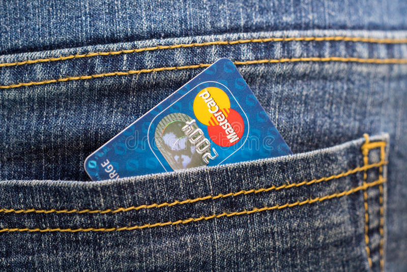 Tarjeta de crédito Mastercard en el bolsillo trasero de vaqueros fotografía de archivo