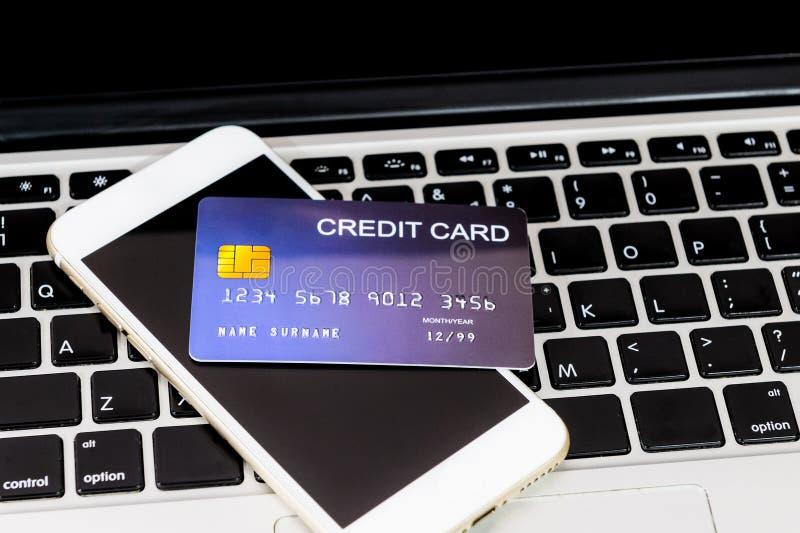 Tarjeta de crédito puesta al lado del teléfono móvil en el teclado del ordenador portátil foto de archivo