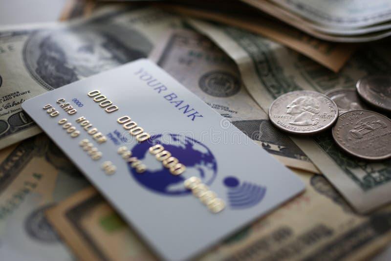 Tarjeta de crédito que miente en la cantidad grande de moneda de los E.E.U.U. imagen de archivo