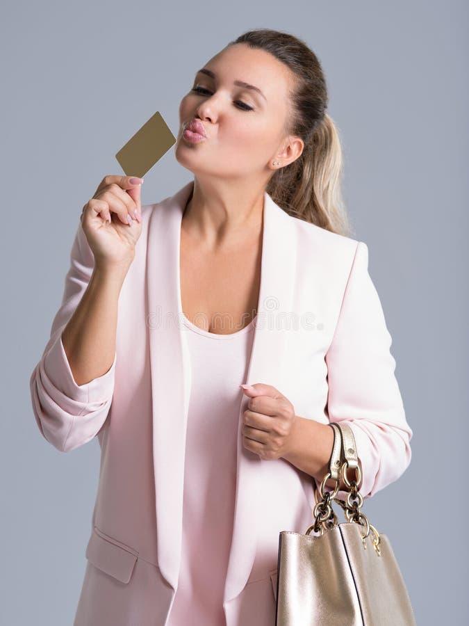 Tarjeta de crédito sorprendida emocionada alegre de la mujer que se besa joven imagenes de archivo