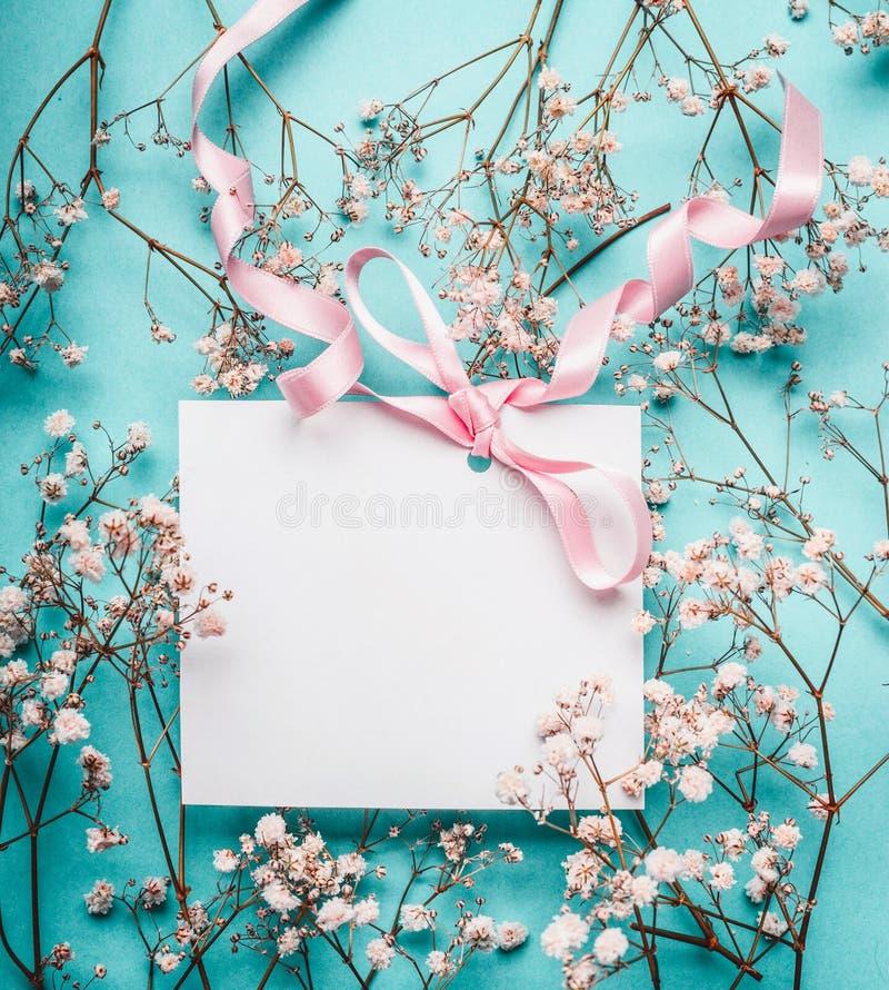 Tarjeta de felicitación blanca en blanco con la cinta rosada en las pequeñas flores blancas en el fondo de los azules turquesa imagen de archivo libre de regalías