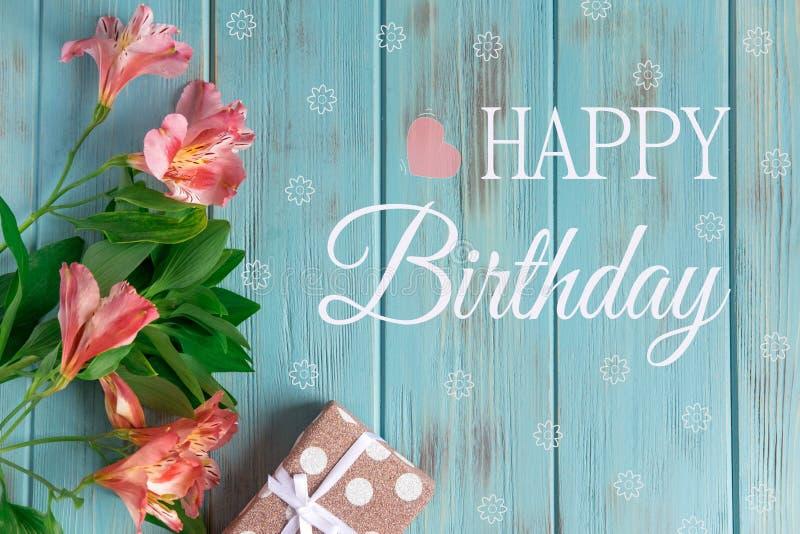 Tarjeta de felicitación con el feliz cumpleaños de la inscripción Saludo congratulatorio a la muchacha, a la madre con las flores imagen de archivo
