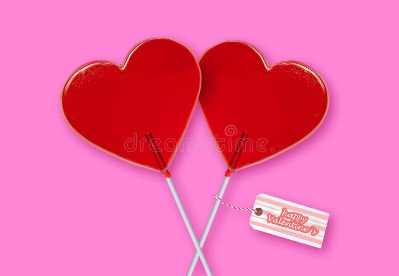 Tarjeta de felicitación de día de San Valentín del papel de empapelar con los pares de las piruletas rojas de la forma del corazó fotos de archivo libres de regalías