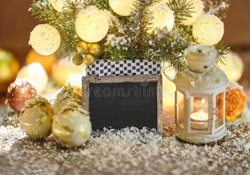 Tarjeta de felicitación de la Navidad con las chucherías, la linterna y el letrero imagenes de archivo