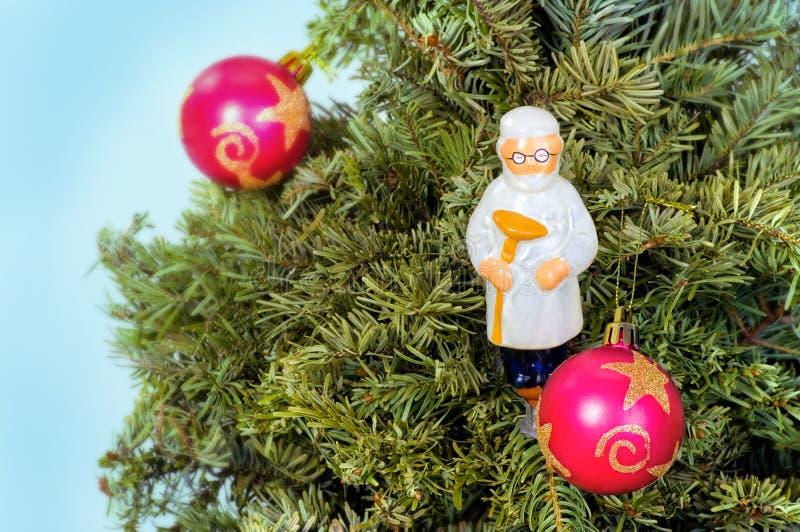 Tarjeta de felicitación de la Navidad del Año Nuevo con el árbol, doctor de los juguetes de la medicina fotografía de archivo